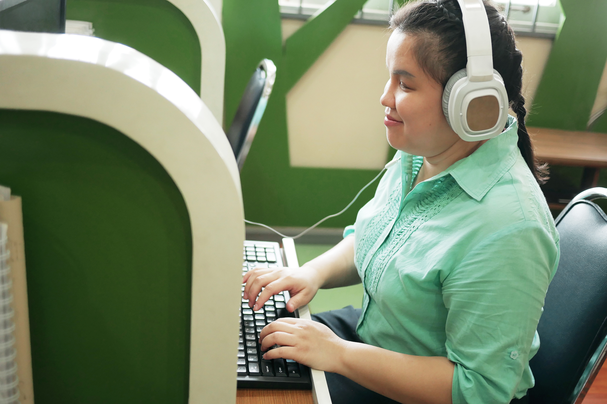 visually disabled women happily working at computer with headphones on